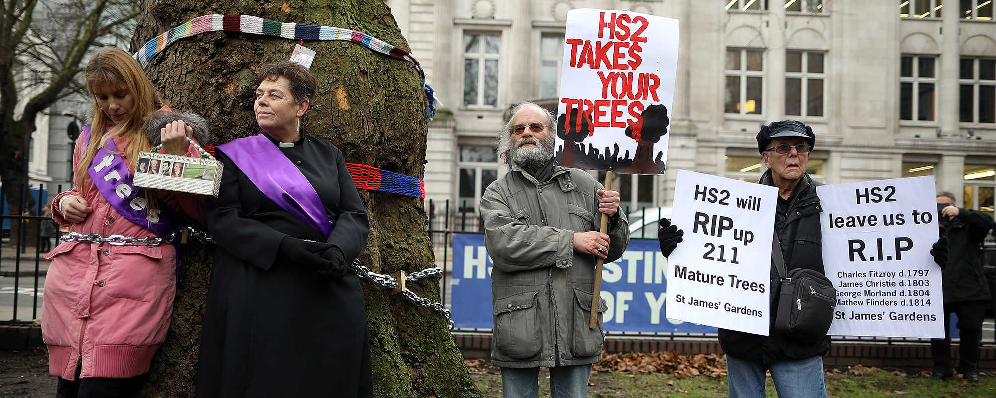Anne Stevens, vicar of St Pancras Church, chains herself to a tree outside Euston Photo: Getty